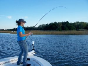 Woman reeling in fish caught inshore on Amelia Island