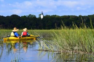 Couple kayaking and looking at lighthouse on Amelia Island
