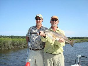Two men holding big fish caught inshore fishing