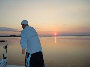 Jeff Crumpton fishing over calm water and sunrise on the horizon