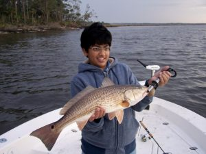 Little boy holding red fish caught inshore at Fernandina Beach
