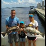 Family each holding fish caught offshore on Fernandina Island Fishing Guide Charter