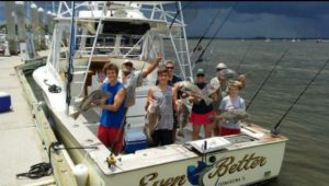 Family standing in boat each holding fish caught offshore on Amelia Island Fishing Guide Charter