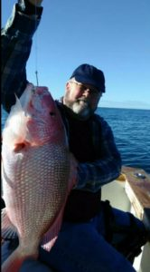 Man standing in boat holding fish caught on Amelia Island Fishing Guide Charter