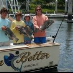 Family holding fish caught on Fernandina Beach Fishing Charter Good day of fishing at Fernandina Beach Family members each holding a fish caught on Amelia Island Fishing Charter trip