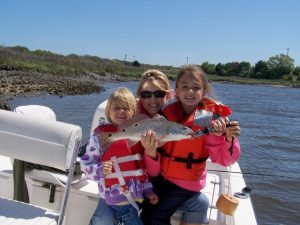 Mother and two daughters holding a redfish caught inshore at Fernandina Beach