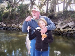 Man hugging little girl holding a redfish caught inshore at Fernandina Beach