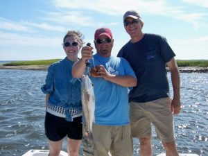 Man standing with 2 others on boat holding a redfish caught inshore at Fernandina Beach