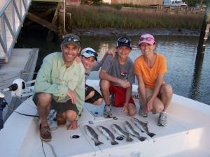 Family on boat showing trout caught inshore at Fernandina Beach