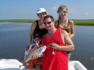 Family on boat holding fish caught inshore at Fernandina Beach