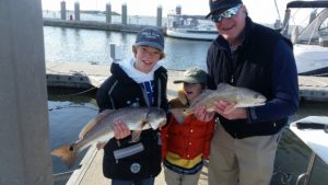Two boys each catch a fish at Amelia Island Charters Island Charters