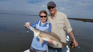 Woman showing fish she caught at Amelia Island Charters