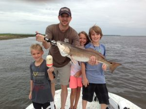 Dad and 3 children catch fish at Amelia Island Charters