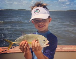 Young boy holding fish caught offshore Amelia Island