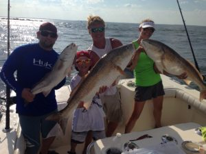 Three men each holding a big fish caught off the coast of Amelia Island