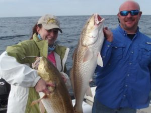 Couple holding fish caught on Fernandina Beach Fishing Charter