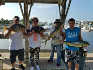 Four men on pier holding gulf stream mahi fish
