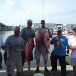 Six men on pier holding red snapper fish