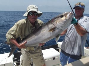 Two men holding large fish on charter boat