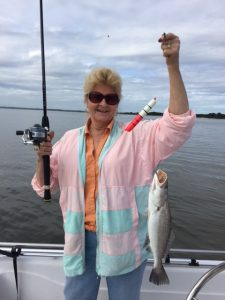 Woman on boat holds up fish she just caught.