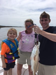 Three family proudly display a fish caught at Fernandina Beach
