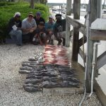 Men displaying vermillion, snapper, sea bass, and trigger fish.
