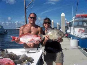 Couple standing on pier each holding a big fish they caught at Amelia Island