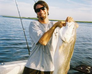 Man on boat holding big fish caught at Fernandina Beach