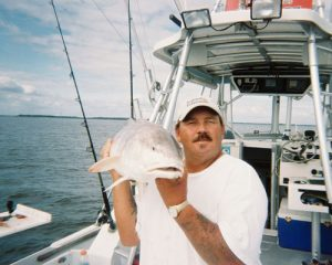 Captain Bill Supplee on boat holding large fish on his shoulder