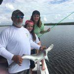 Captain Pat holding shark beside two smiling fishermen