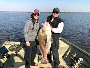 Man and Woman holding Big Black Drum caught Amelia Island Charter Fishing