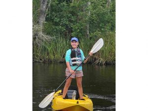 Kerri Foster standing on kayak at Amelia Island