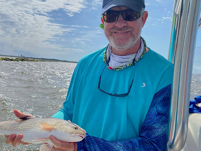 Captain Bart Smith of Fernandina Fishing Charters standing on boat holding a fish.
