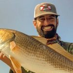 Captain Jerimiah Joost-Miller Smiling and Holding a Big Fish